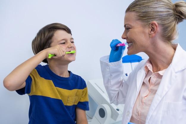 Dentista feliz e menino escovando os dentes contra a parede