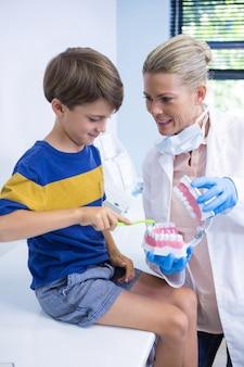 Dentista feliz ensinando menino escovando dentes