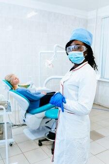 Dentista fêmea afro-americano de sorriso dos jovens na frente do paciente na clínica. conceito de clínica dentária.