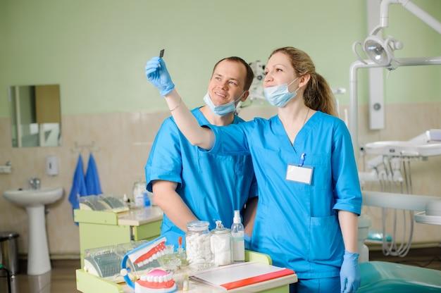 Dentista fêmea bonito novo que mostra um raio x ao colega masculino no escritório dental da clínica. conceito de procedimento oral