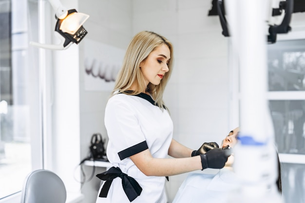 Dentista fêmea consideravelmente novo que faz o exame e o tratamento para o paciente fêmea novo na clínica dental.