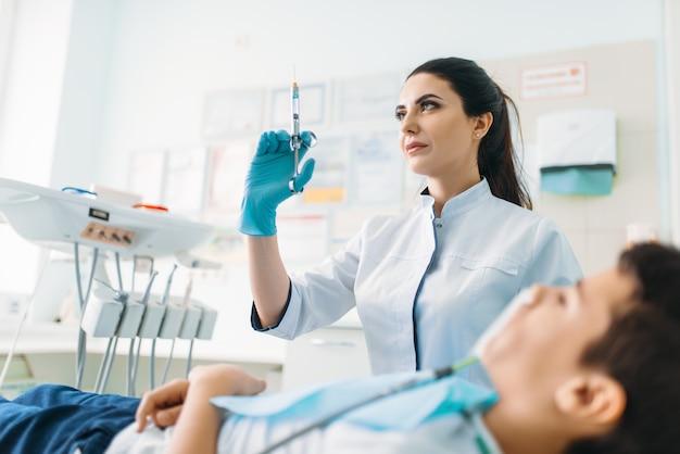 Dentista feminina com seringa, odontopediatria