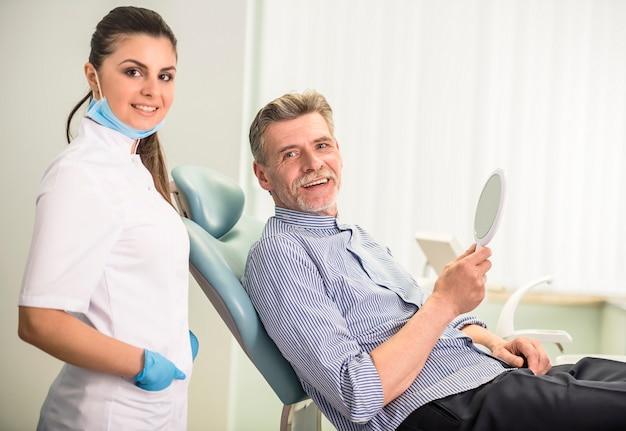 Dentista feminina com seu cliente sênior na clínica odontológica.