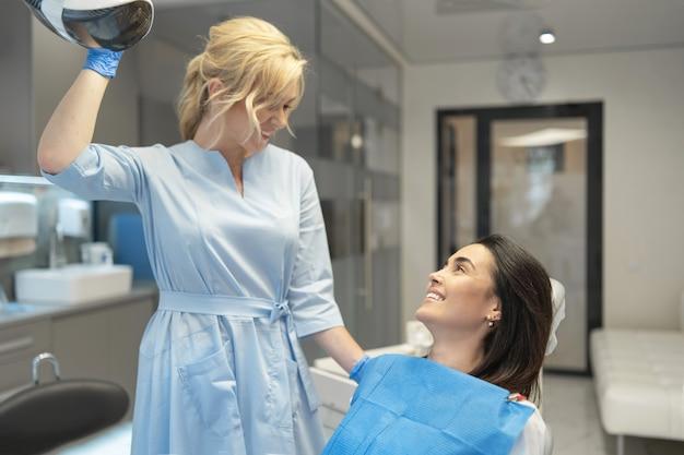 Dentista feminina em clínica odontológica fornecendo exame e tratamento da cavidade oral para paciente