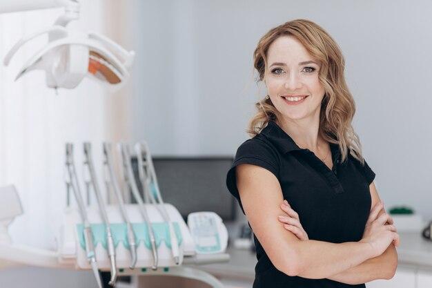 Dentista feminina em pé em sua clínica e olhando