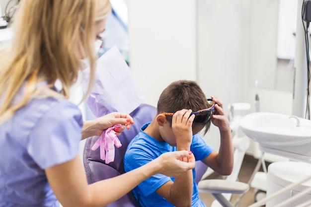 Dentista feminina em pé perto de menino, removendo os óculos de segurança