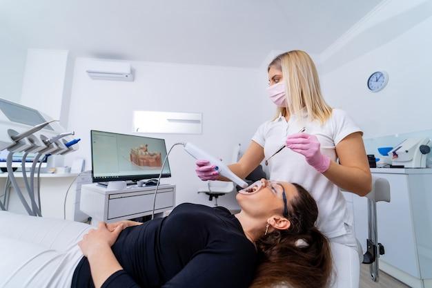 Dentista feminina está trabalhando na clínica de estomatologia moderna. instrumento estomatológico na clínica odontológica. clareamento dos dentes.