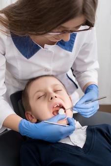 Dentista feminina examina os dentes da criança paciente