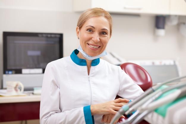 Dentista feminina madura feliz sorrindo para a câmera, posando em seu escritório