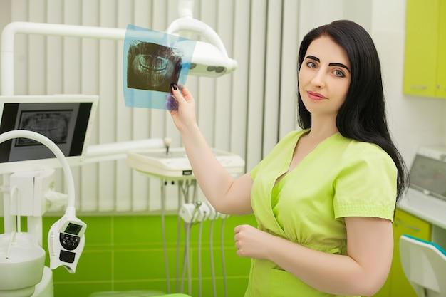Dentista feminina no consultório odontológico, examinando os dentes do paciente
