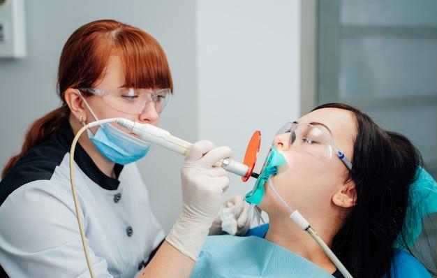 Dentista feminina que trata os dentes da mulher paciente. médico de estomatologia, tratamento de dentes de mulher na clínica de odontologia