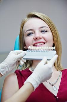 Dentista feminina talentosa que descobre qual é a cor dos dentes correspondente para seu paciente.