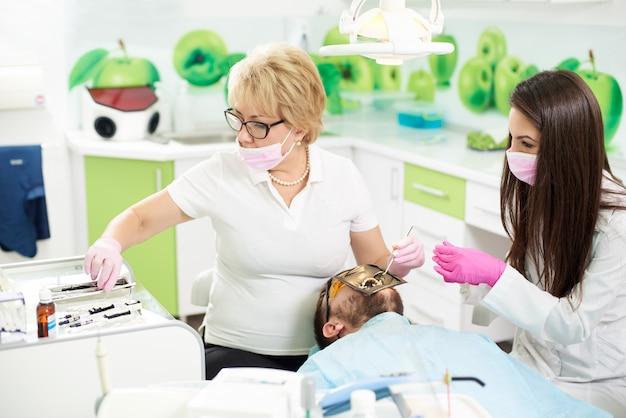 Dentista feminina trabalhando em um paciente do sexo masculino usando um cofre. jovem assistente ajuda na odontologia no hospital com novas tecnologias