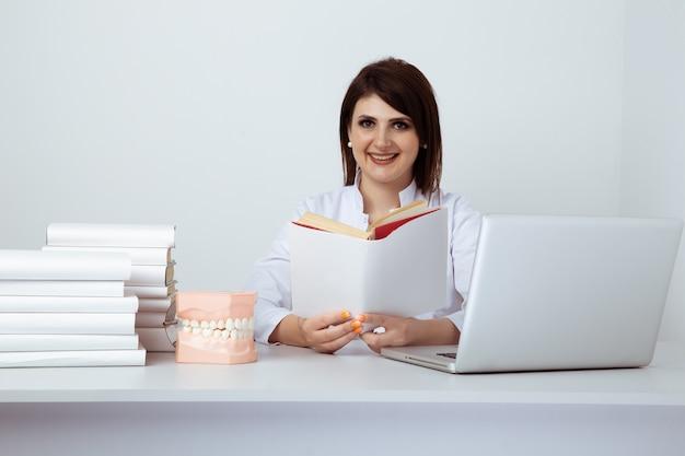 Dentista feminino de uniforme sentado à mesa e trabalhando com a equipe odontológica no escritório.