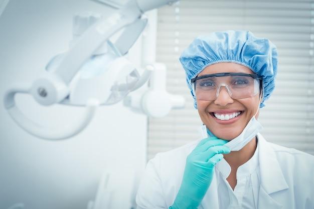 Dentista feminino que usa boné cirúrgico e óculos de segurança