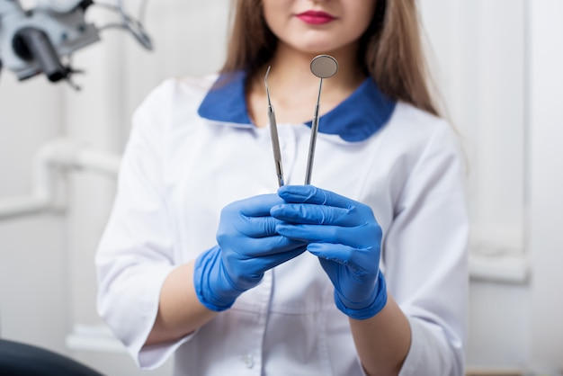 Dentista feminino segurando ferramentas - espelho dental e sonda dental no consultório odontológico