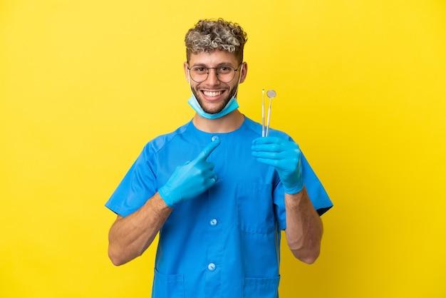 Dentista homem caucasiano segurando ferramentas isoladas em um fundo amarelo apontando para o lado para apresentar um produto
