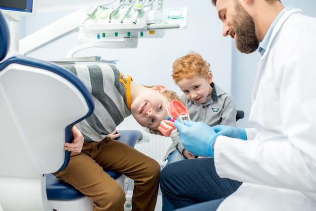 Dentista infantil mostrando aos meninos como escovar dentes em mandíbulas artificiais no consultório odontológico