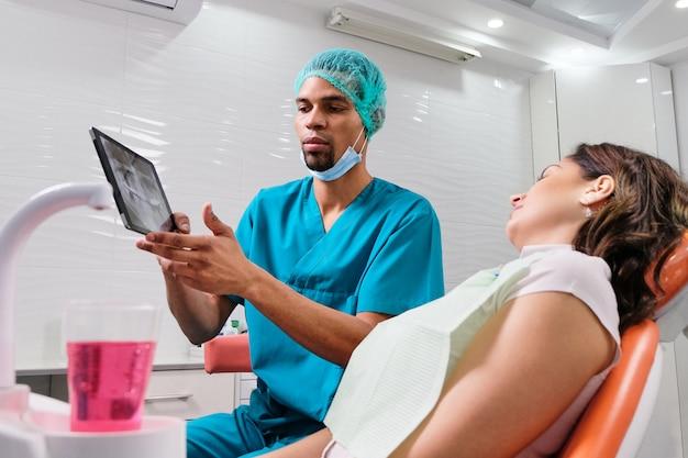 Dentista masculina africana, explicando o raio-x para o paciente
