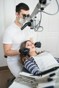 Dentista masculina com ferramentas odontológicas - microscópio, espelho e sonda tratando os dentes do paciente no escritório da clínica odontológica