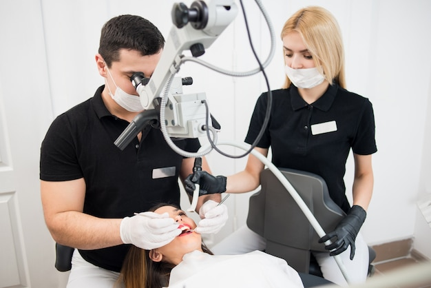 Dentista masculina e assistente feminina tratando os dentes do paciente com ferramentas dentárias