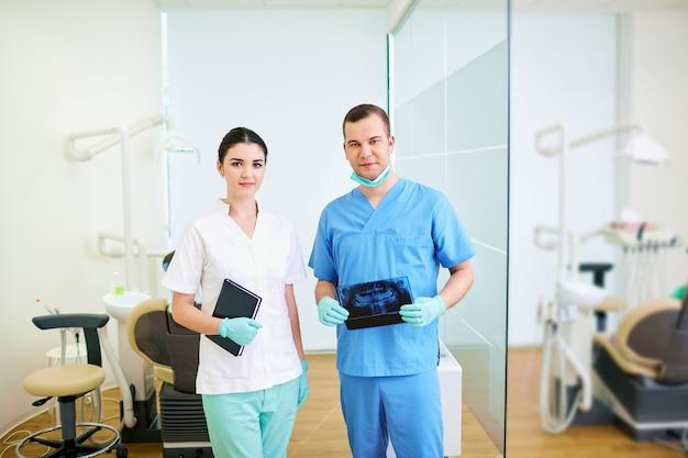 Dentista masculina e assistente mulheres no local de trabalho um consultório odontológico
