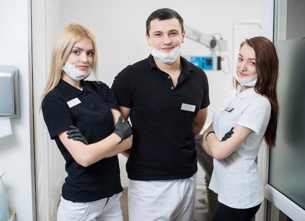 Dentista masculina e duas assistentes femininas no consultório odontológico