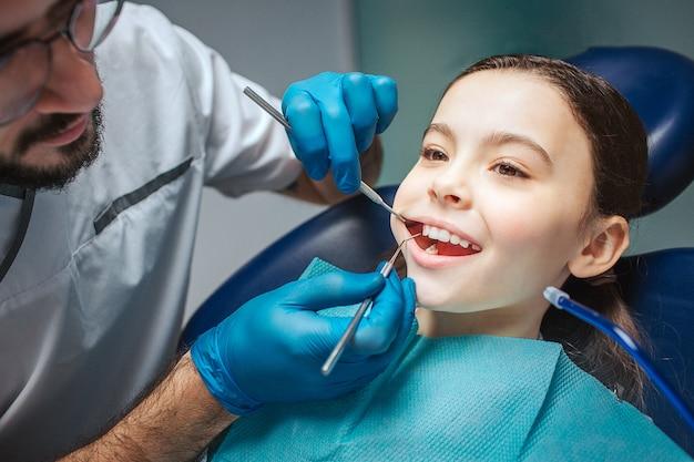 Dentista masculina fazendo check-up da boca da menina