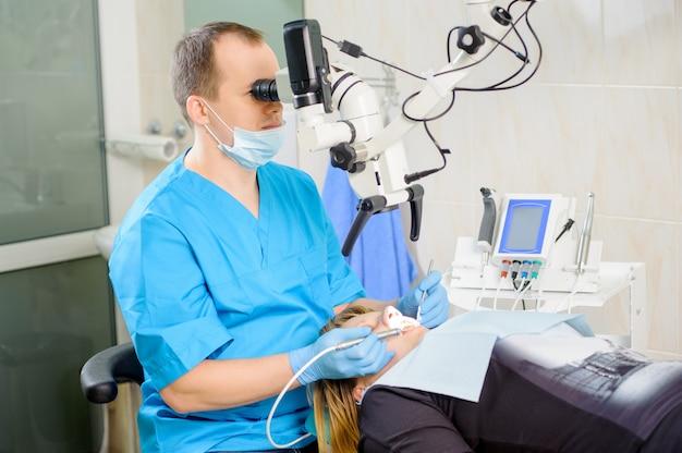Dentista masculina trabalhando com microscópio na clínica moderna dentista