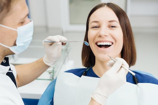 Dentista masculino, branco, examinando os dentes de uma jovem paciente na clínica odontológica