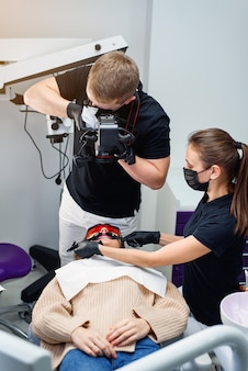 Dentista masculino com assistente tira uma foto intraoral dos dentes de uma paciente sentada na cadeira odontológica.