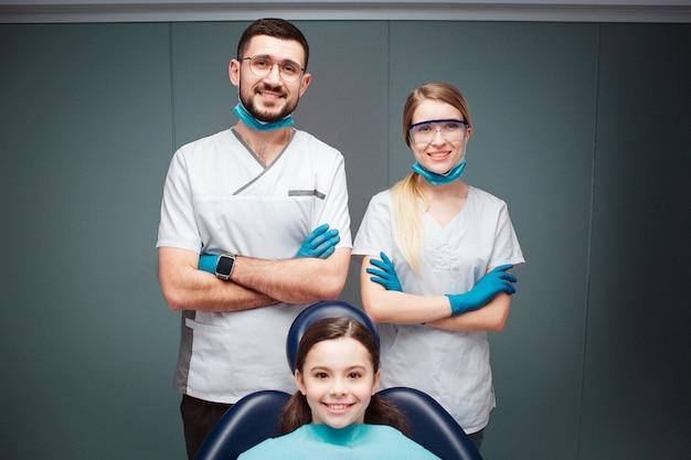 Dentista masculino e fêmea positivo agradável com a menina na cadeira dental. eles parecem retos e sorriem. os adultos cruzam as mãos. isolado em verde.