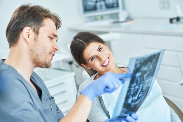 Dentista masculino e mulher discutindo resultados de raio-x em consultório dentista