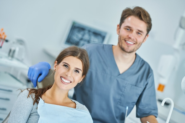 Dentista masculino e mulher em consultório dentário