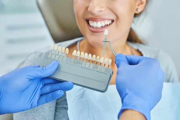 Dentista masculino e mulher na clínica odontológica escolhendo o tom do implante
