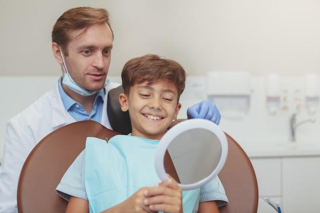 Dentista masculino maduro e seu jovem paciente, verificando resultados de atendimento odontológico