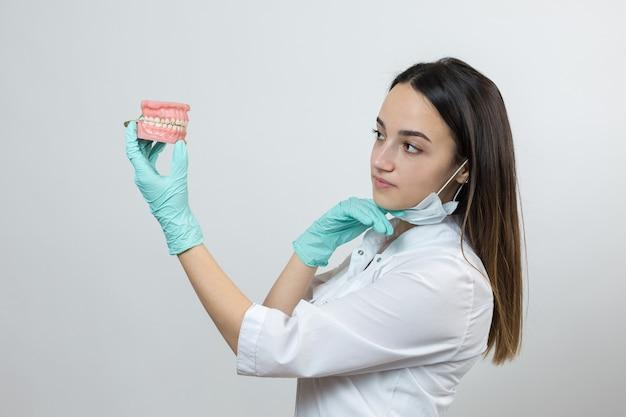 Dentista médica com um jaleco branco faz uma simulação de dentes.