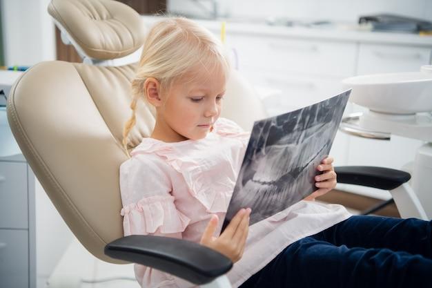 Dentista mostra um pequeno paciente um raio-x dos dentes