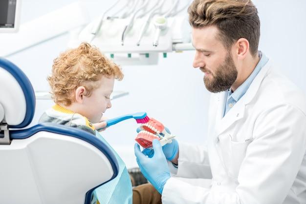 Dentista mostrando ao menino como escovar os dentes na mandíbula artificial no consultório odontológico