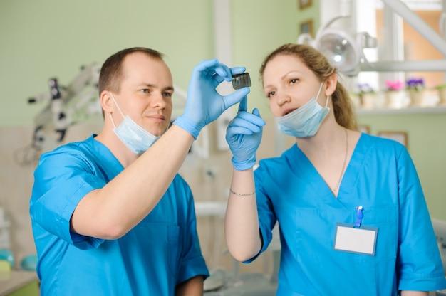 Dentista, mostrando o raio-x para assistente no consultório odontológico