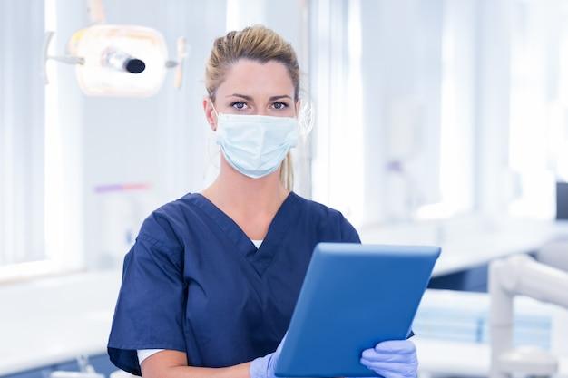 Dentista na máscara usando seu tablet e olhando para a câmera