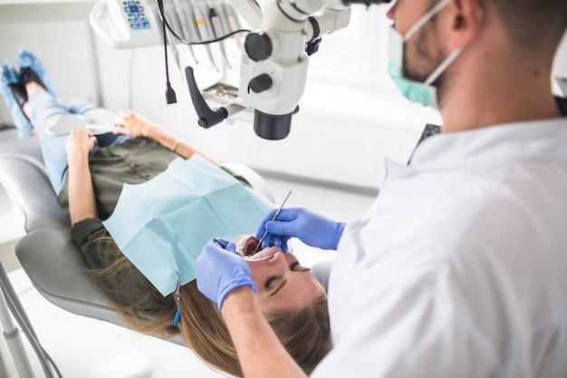 Dentista operando paciente do sexo feminino com microscópio odontológico em clínica