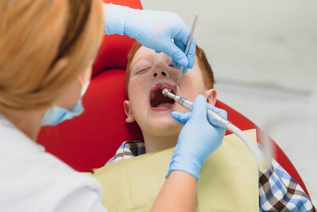Dentista pediatra examinando os dentes de um garotinho na cadeira do dentista na clínica odontológica