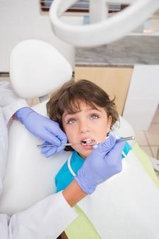 Dentista pediatra que examina os dentes dos rapazes pequenos na cadeira dos dentistas