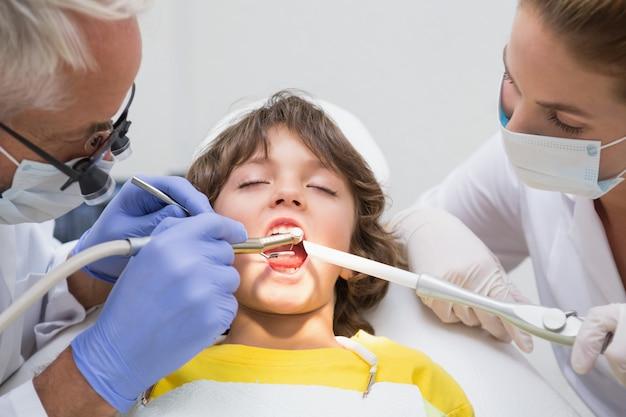 Dentista pediátrica e assistente examinando um pouco dentes de meninos