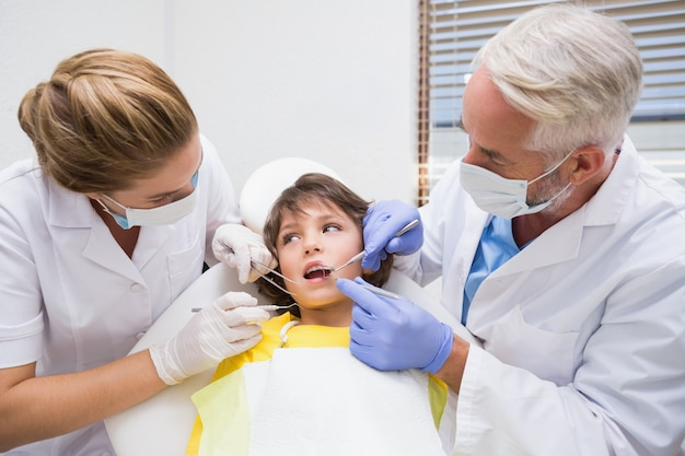 Dentista pediátrica examinando um pouco dentes de meninos com seu assistente