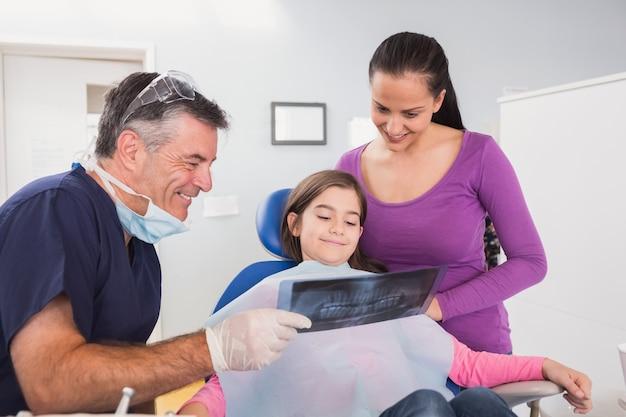 Dentista pediátrica, explicando a mãe e sua filha o raio-x