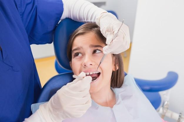 Dentista pediátrica fazendo exame em um paciente jovem com medo