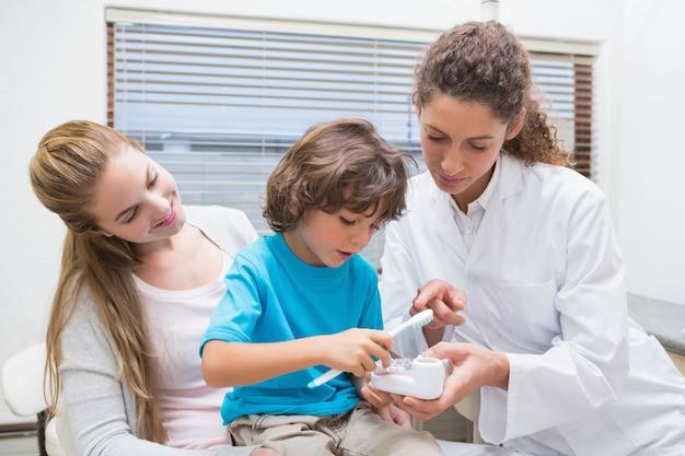 Dentista pediátrica mostrando garotinho como escovar os dentes com sua mãe na clínica odontológica