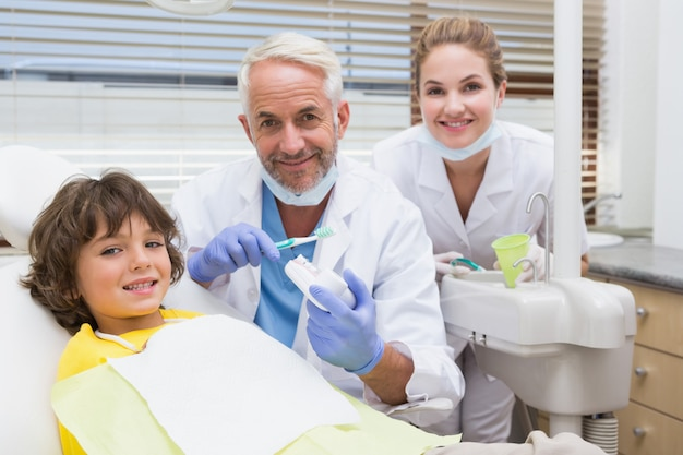 Dentista pediátrica mostrando garotinho como escovar os dentes